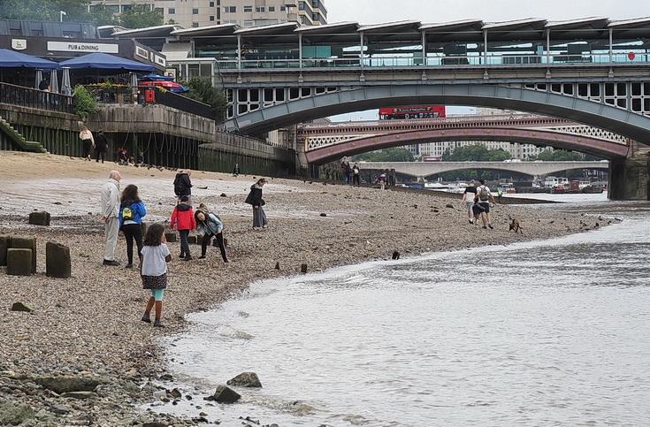 The River Thames at low tide: mudlarkers, sunbathers and bridges