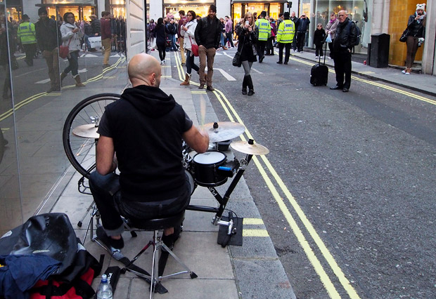 Puncture Kit busker plays on a drum kit made from a bicycle in central London