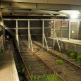 The former Thameslink railway tracks running through Barbican station now lie abandoned and covered in weeds, with metal gates blocking access at each end.