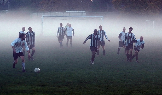 Ghostly football - players hunt the ball in the swirling mists of Surrey